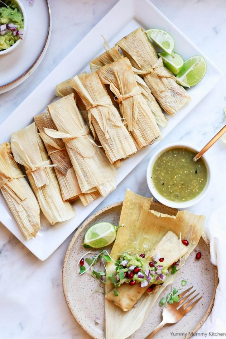 Easy homemade vegetarian or vegan tamales made with Mexican masa, black beans, chilies, and cheese. Beautiful homemade tamales on a platter next to an open tamale on a plate served with salsa verde and guacamole.