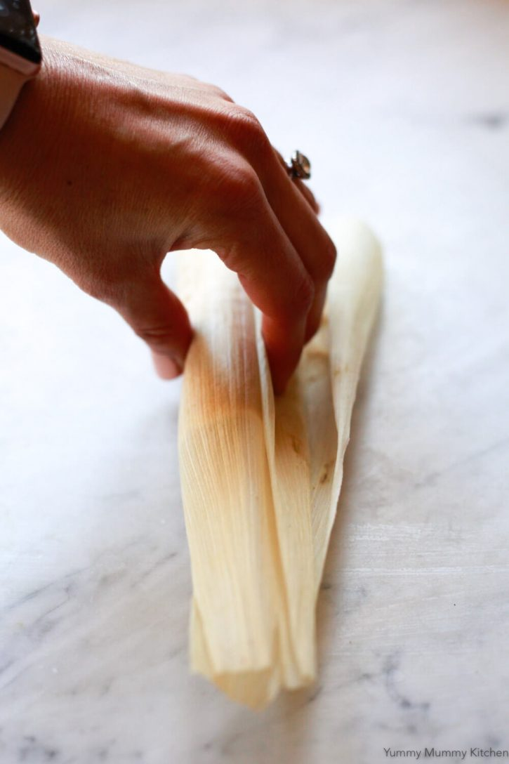 A corn husk is wrapped over tamale filling. An image showing how to wrap tamales.
