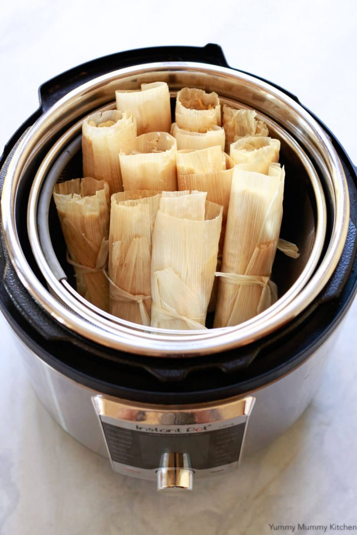 Tamales sit in the steamer basket of an Instant Pot pressure cooker ready to steam.