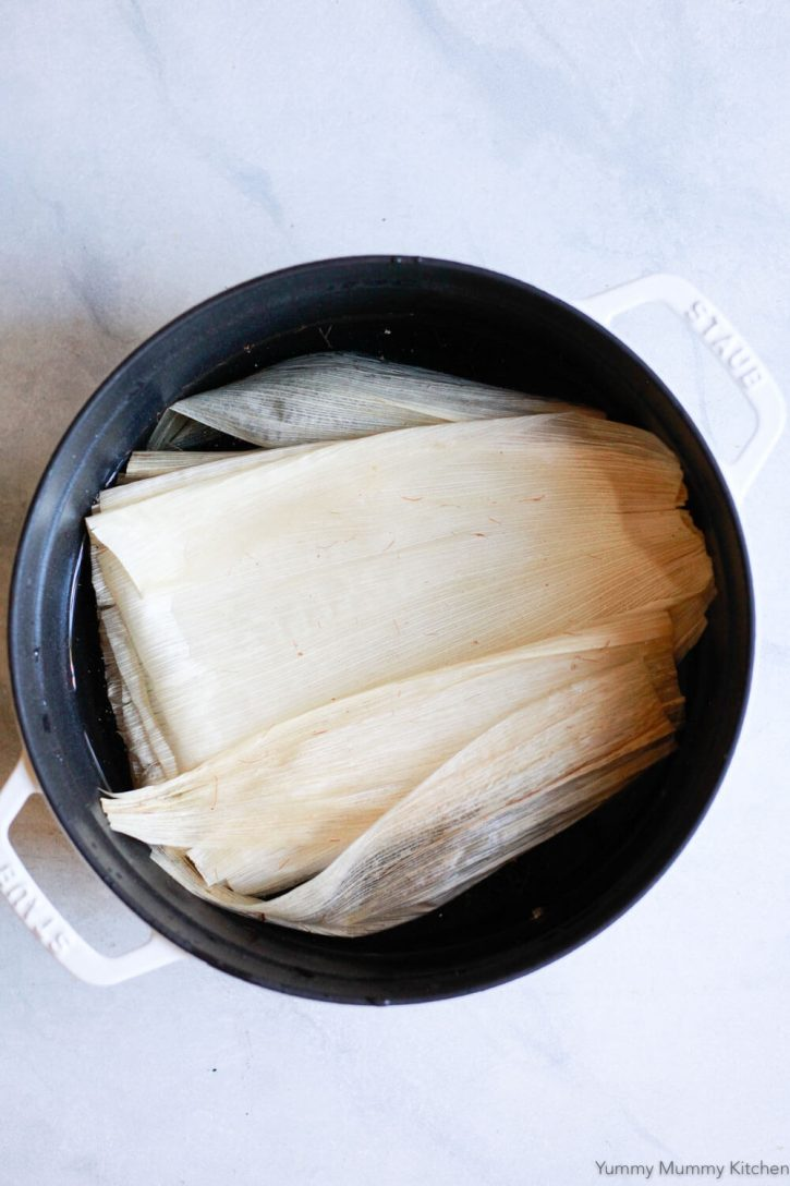 Corn husks soak in a large pot to prepare for making tamales.