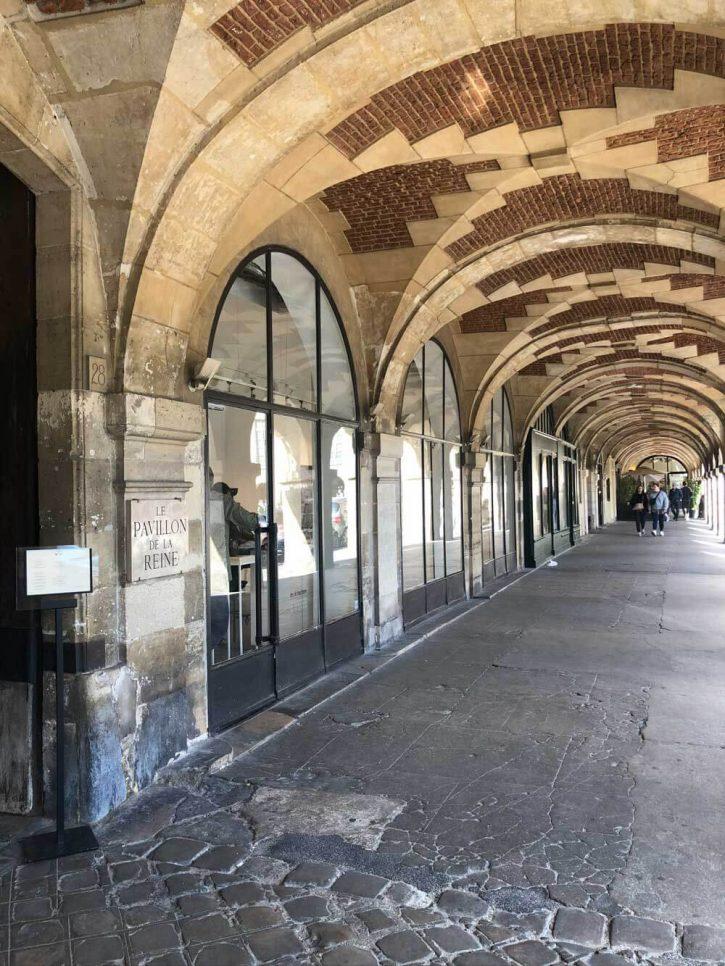 The entrance to the Pavillon de la Reine hotel in the Place des Vosges arcade, Paris France.