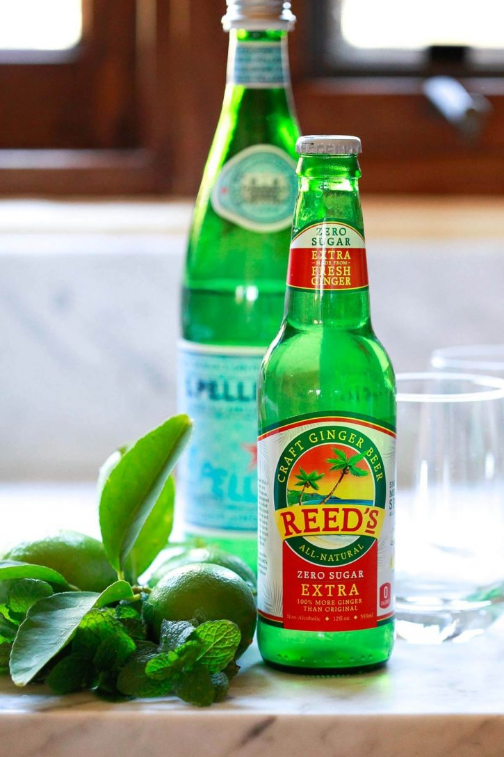 A bottle of Reed's ginger beer on a countertop with mint and fresh limes to make mocktails.