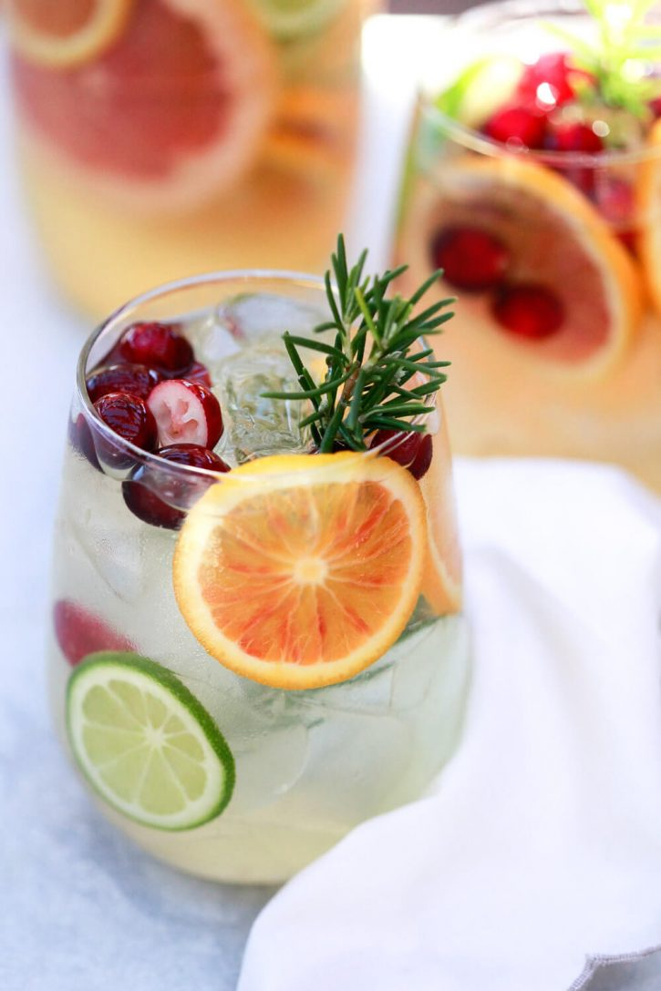 A glass of winter white sangria with orange slices, rosemary, and cranberries. This sangria recipe is made in a pitcher and perfect for holiday parties.