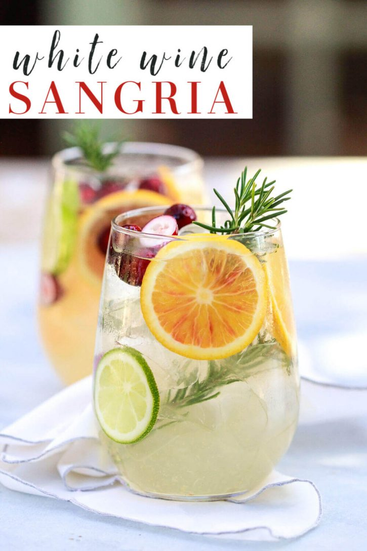 A beautiful glass of white sangria with orange and lime slices and garnished with rosemary. This easy white wine sangria recipe is perfect for fall and winter.