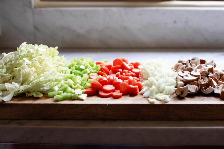 A cutting board with shredded cabbage, chopped celery, carrots, onion, and mushrooms. These vegetables are being prepped for a vegetable soup with cabbage.