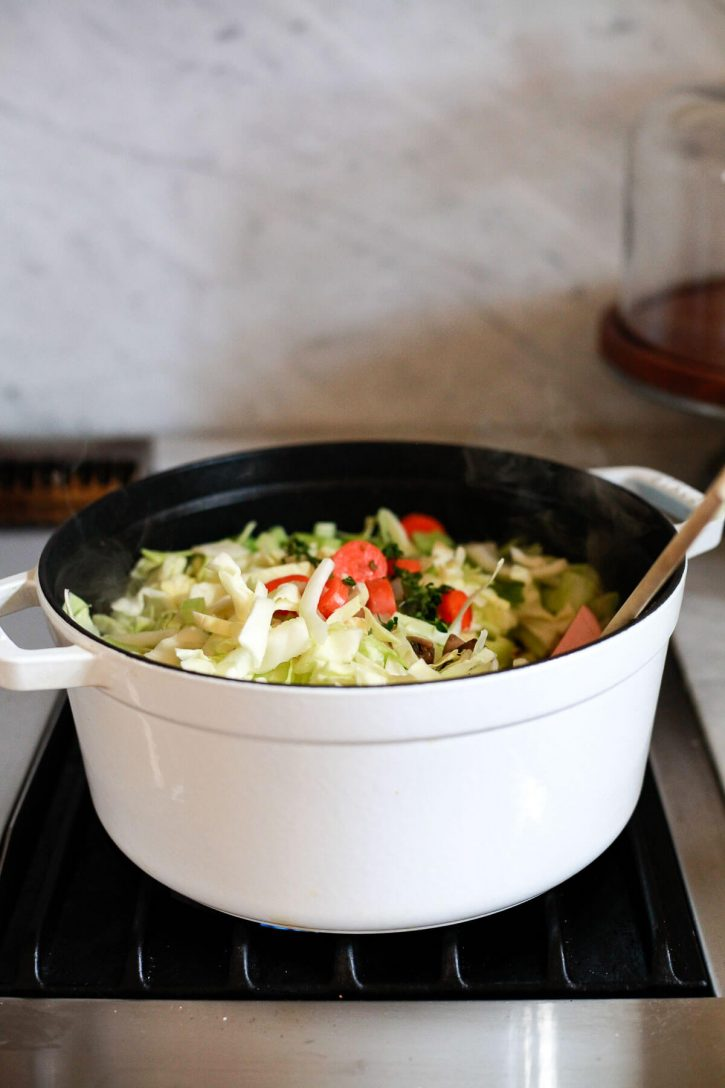 A white Staub pot filled with vegetables and shredded cabbage to make a cabbage soup diet recipe for weight loss and detox.