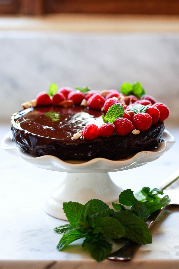 A beautiful vegan chocolate ganache cake topped with raspberries, mint, and nuts.