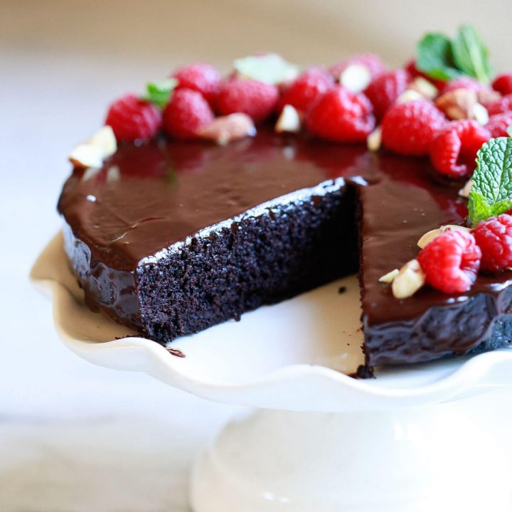 A beautiful vegan chocolate cake with ganache and raspberries.