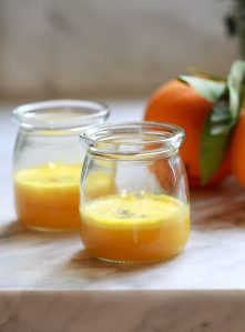 Two small glass jars filled with homemade turmeric wellness shots.