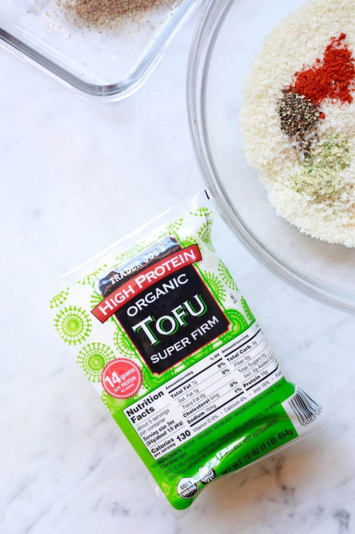 A block of Trader Joe's high protein organic super firm tofu sits on a countertop next to panko breadcrumbs for making tofu nuggets.