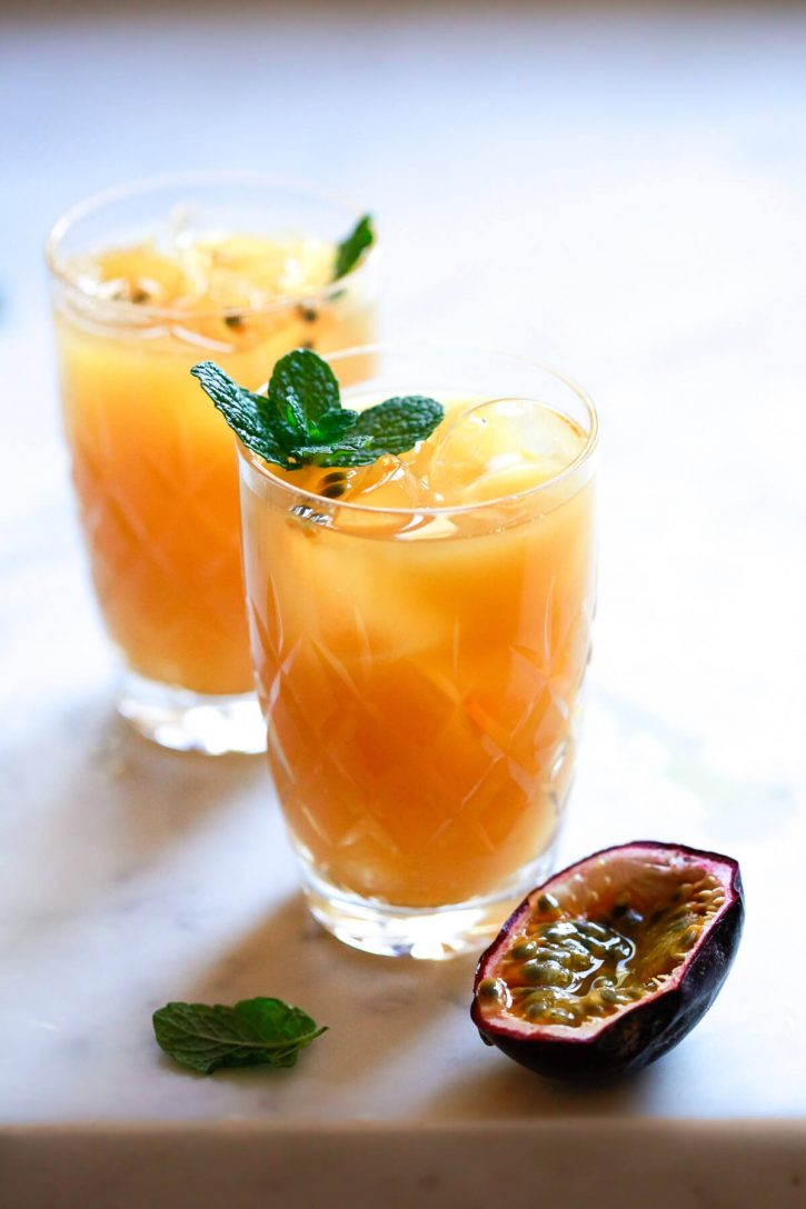 Crystal glasses filled with homemade passion fruit juice garnished with passion fruit (lilikoi) seeds and fresh mint.