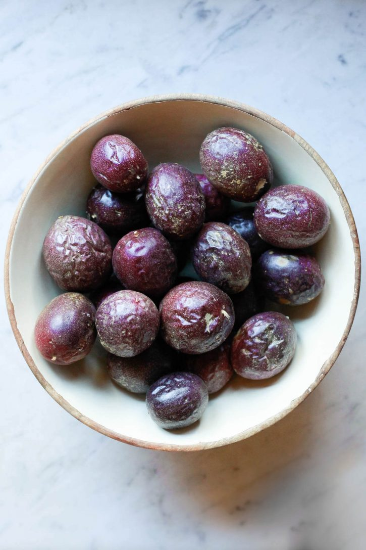 A large bowl filled with wrinkled ripe purple passion fruit sits on a marble countertop.