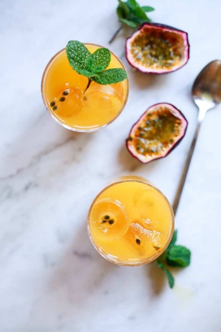 Two glasses filled with passion fruit juice. A halved passion fruit sits in the background on a marble countertop.