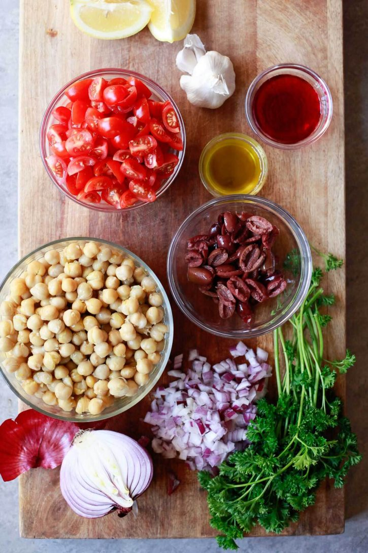 The ingredients for Balela, a Middle Eastern bean salad, in bowls on a cutting board.