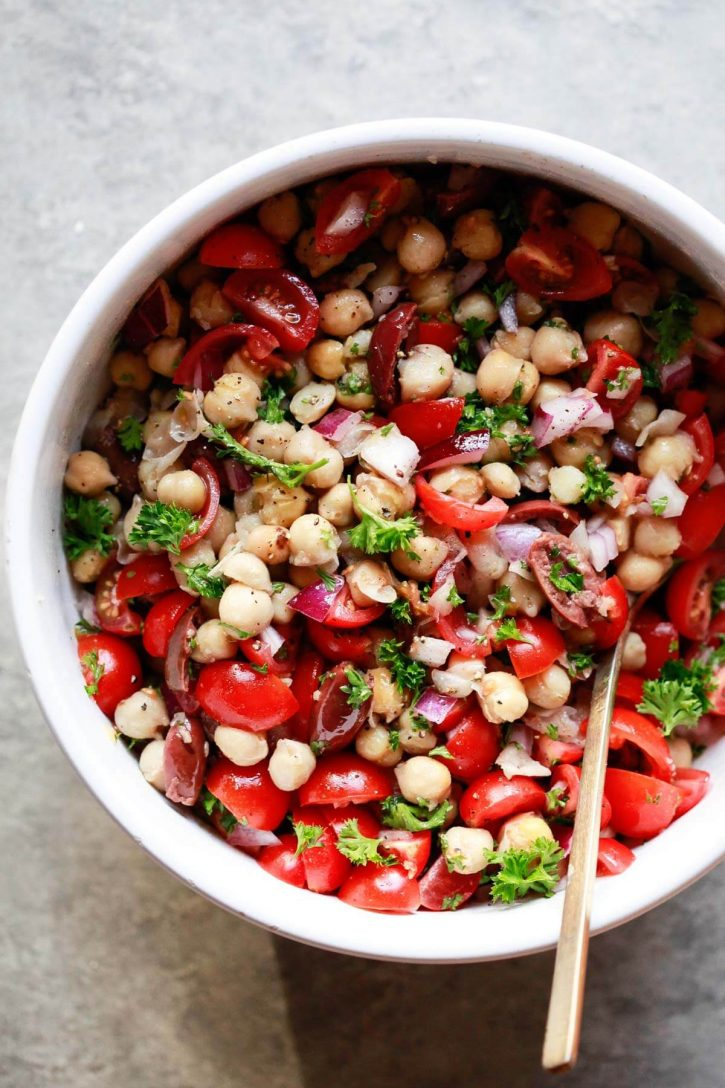 A white bowl filled with Balela, a Middle Eastern chickpea and bean salad with tomatoes, herbs, olives, and onions. A healthy vegetarian, vegan, gluten free recipe.