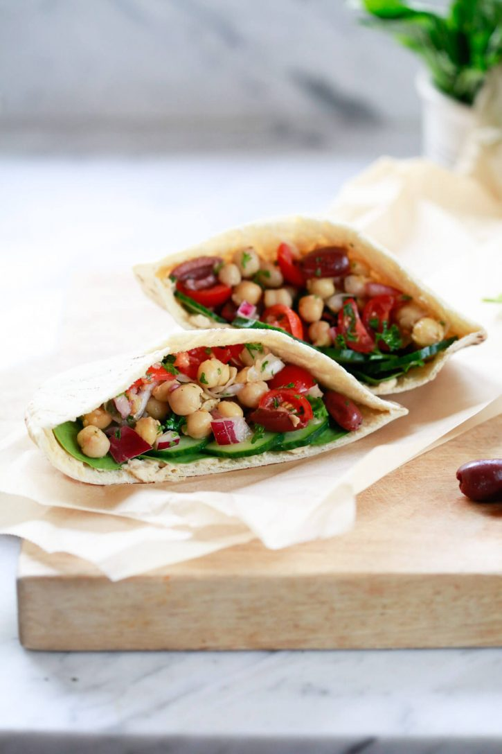 Two pita pockets filled with Balela, a Middle Eastern chickpea bean salad, and hummus and cucumbers.