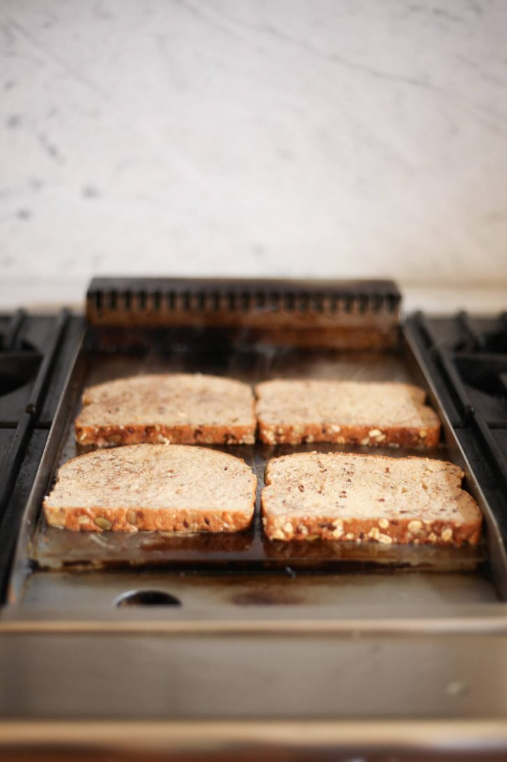 Slices of healthy vegan French toast cook on a griddle.
