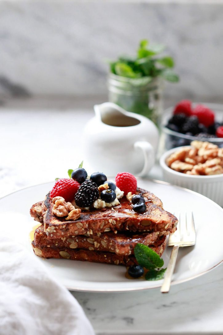Plated healthy vegan french toast topped with berries and walnuts on a plate.