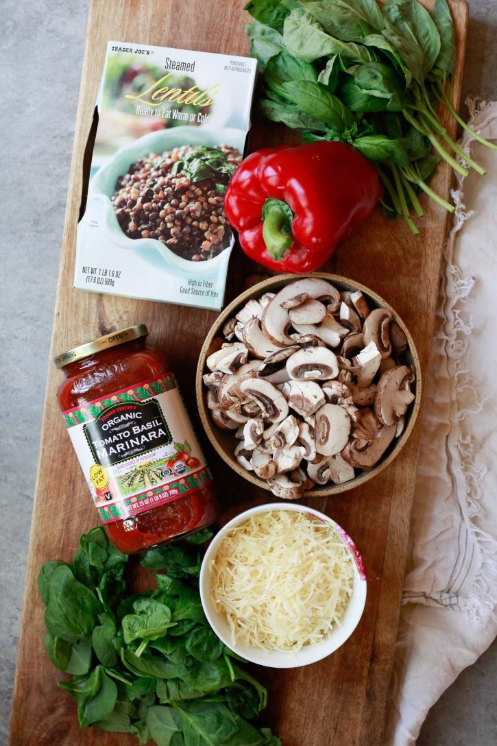 Trader Joe's steamed lentils, marinara, bell pepper, sliced mushrooms, basil, and cheese sit on a cutting board. These are the ingredients for a vegetarian lentil casserole.