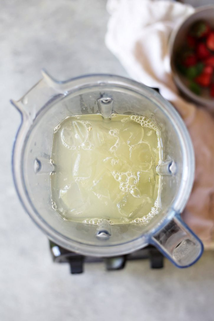 A Vitamix blender is filled with lemon juice, water, sugar, and ice to make blended lemonade.