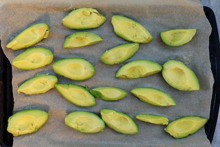 Avocado pieces are pre-frozen on a cookie sheet.