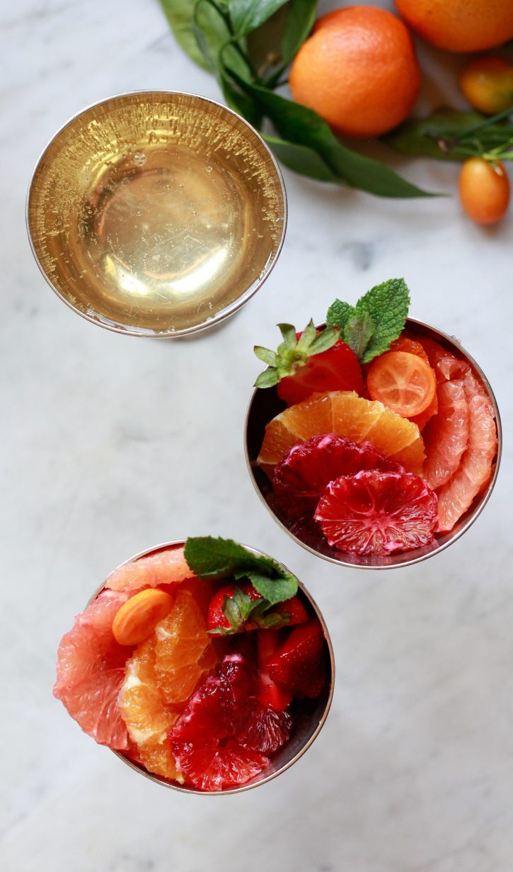 Citrus fruit salad in individual serving dishes with a glass of Champagne. The best winter or spring fruit salad recipe.