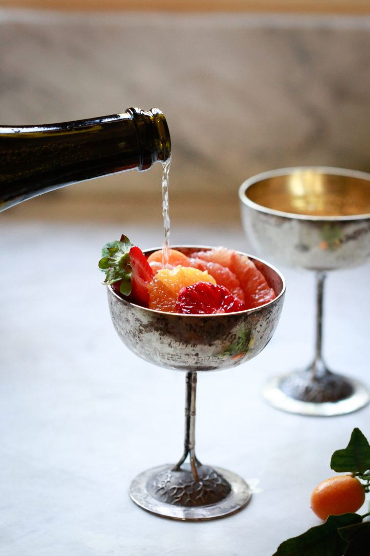 Champagne or prosecco is poured over sliced citrus including grapefruit, orange, and blood orange in tall Champagne coupes.