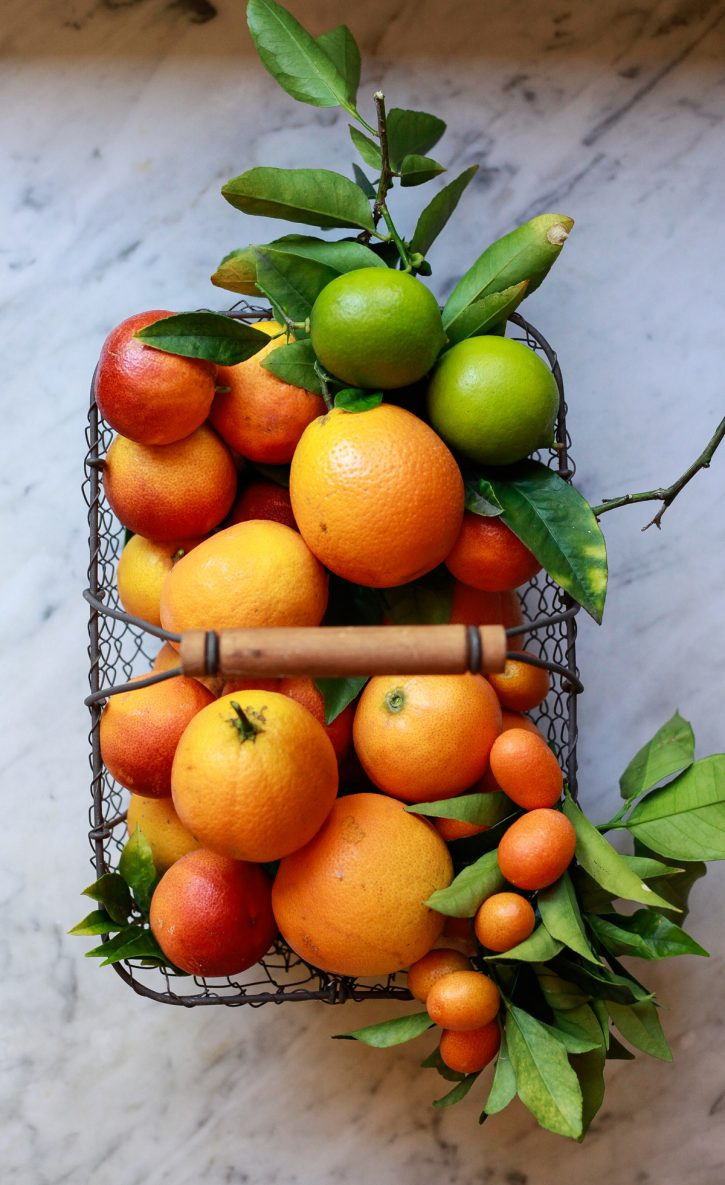 Beautiful photograph of a basket filled with homegrown citrus including oranges, blood oranges, and limes.
