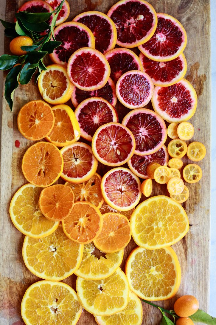 Sliced blood oranges, tangerines, kumquats, and oranges on a cutting board.