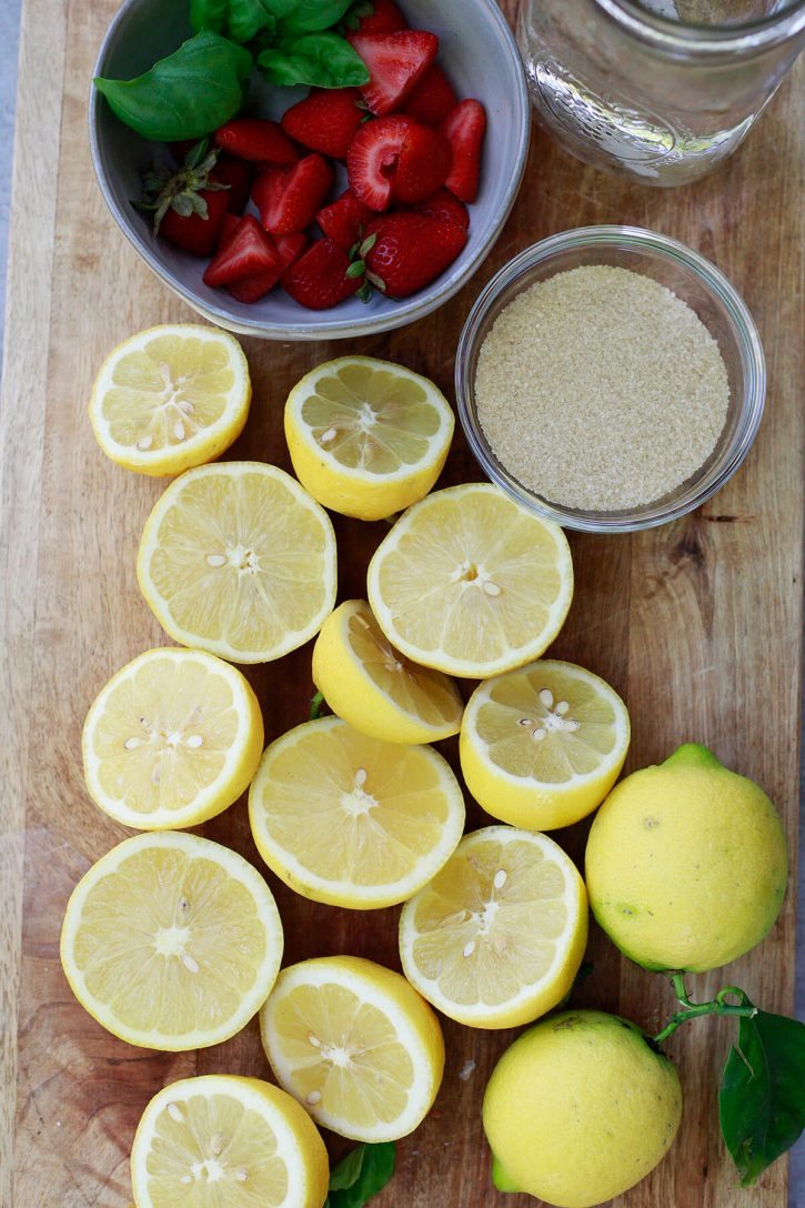 Halved lemons, strawberries, sugar, and water on a cutting board to make homemade strawberry pink lemonade.