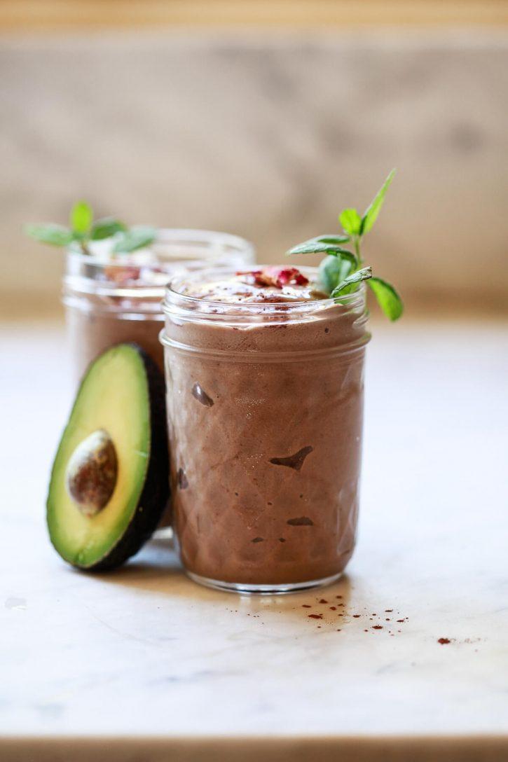 A chocolate banana avocado smoothie on a marble counter sitting next to half of an avocado. A healthy vegan chocolate avocado smoothie recipe.