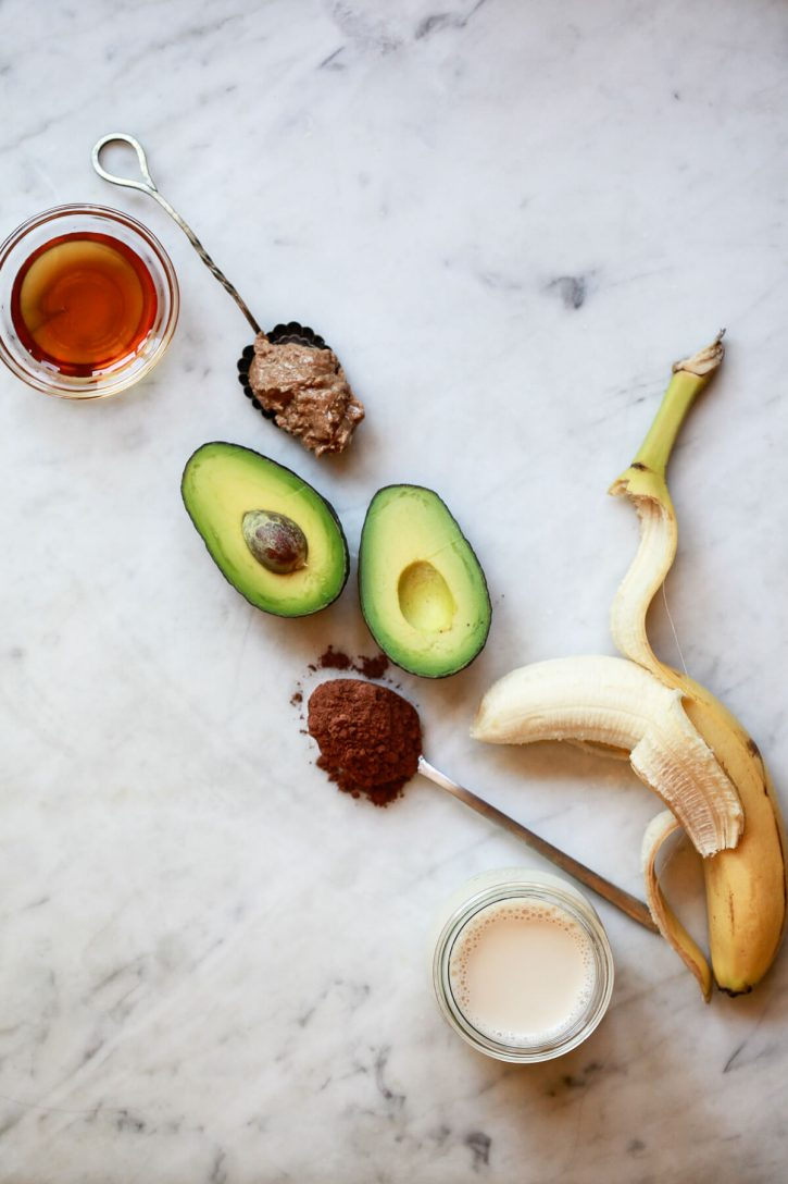 The ingredients for a chocolate banana avocado smoothie on a marble kitchen counter: banana, avocado, cacao powder, almond milk, almond butter, and maple syrup.