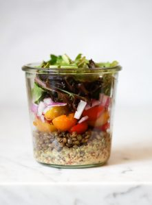 A layered mason jar salad recipe with lentils, tomatoes, onions, and lettuce.