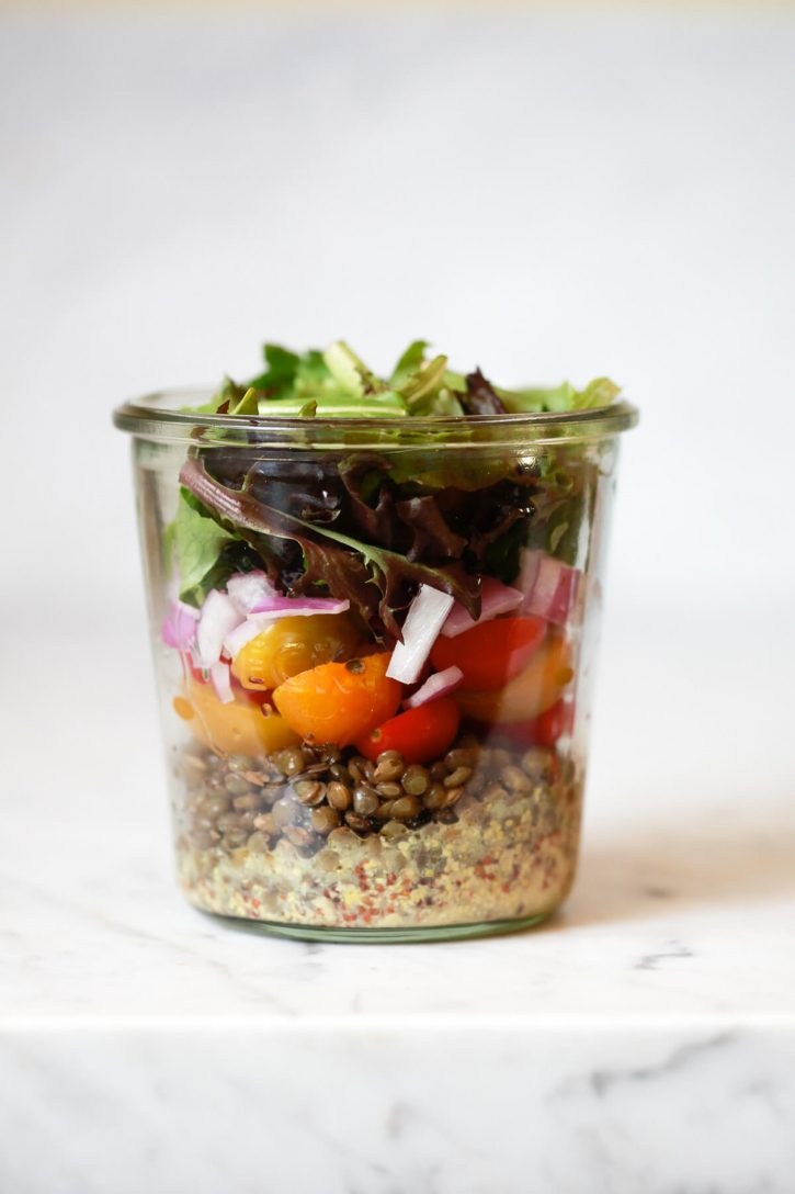 A cold French lentil salad layered in a glass mason jar with mustard vinaigrette, lentils, tomatoes, red onion, and lettuce on top. This beautiful and healthy lentil salad is vegan and gluten free.