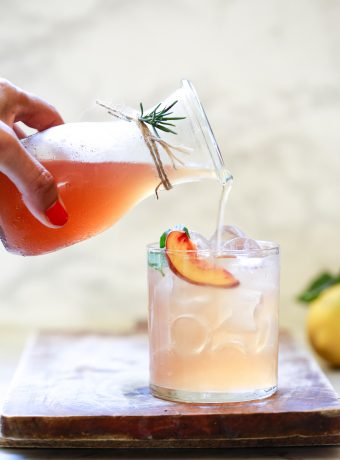 A bottle of a peach shrub drink pours into a glass of ice and water.