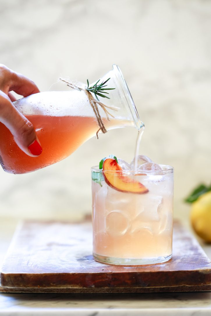 A small jar filled with a peach shrub drink (drinking vinegar) is poured into a glass of ice to make a shrub cocktail.
