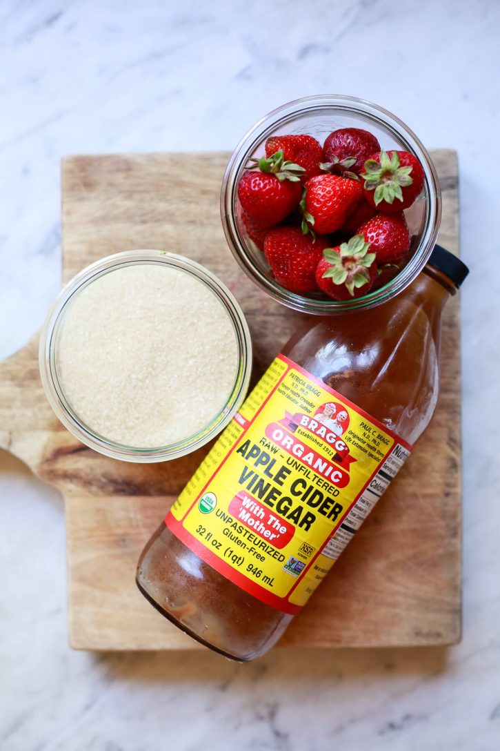 A bottle of Bragg's apple cider vinegar, fresh strawberries, and sugar sit on a counter to illustrate how to make a shrub drink.