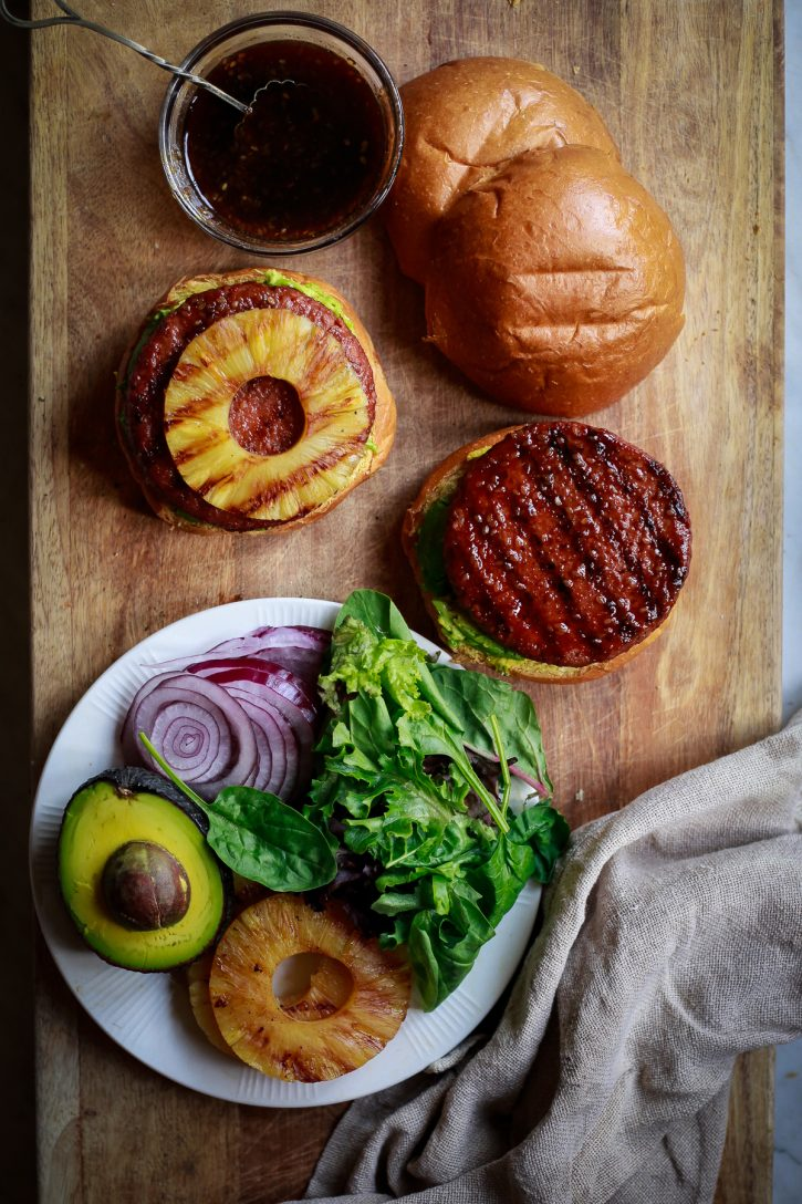 Pineapple teriyaki grilled veggie burgers are assembled on a wooden cutting board. Ingredients include grilled pineapple rings, greens, avocado, and red onion.