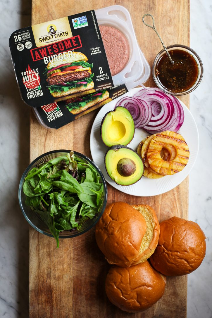 Plant Based vegan hamburger patties, toppings, and buns sit on a cutting board alongside a small bowl of teriyaki sauce.