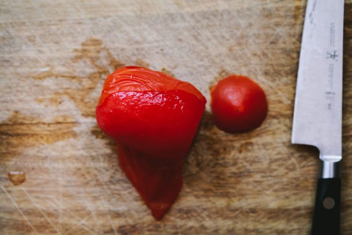 A Roma tomato that has been frozen and thawed is peeled on a cutting board.