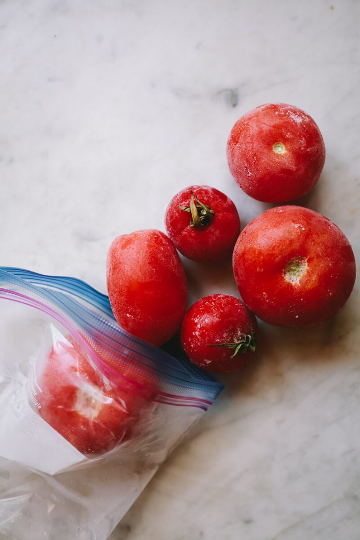 Frozen whole tomatoes come out of a ziplock bag.