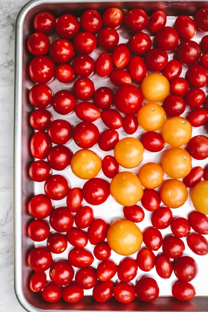 Whole fresh cherry tomatoes sit on a sheet pan before going into the freezer. This is the first step in how to freeze cherry tomatoes.