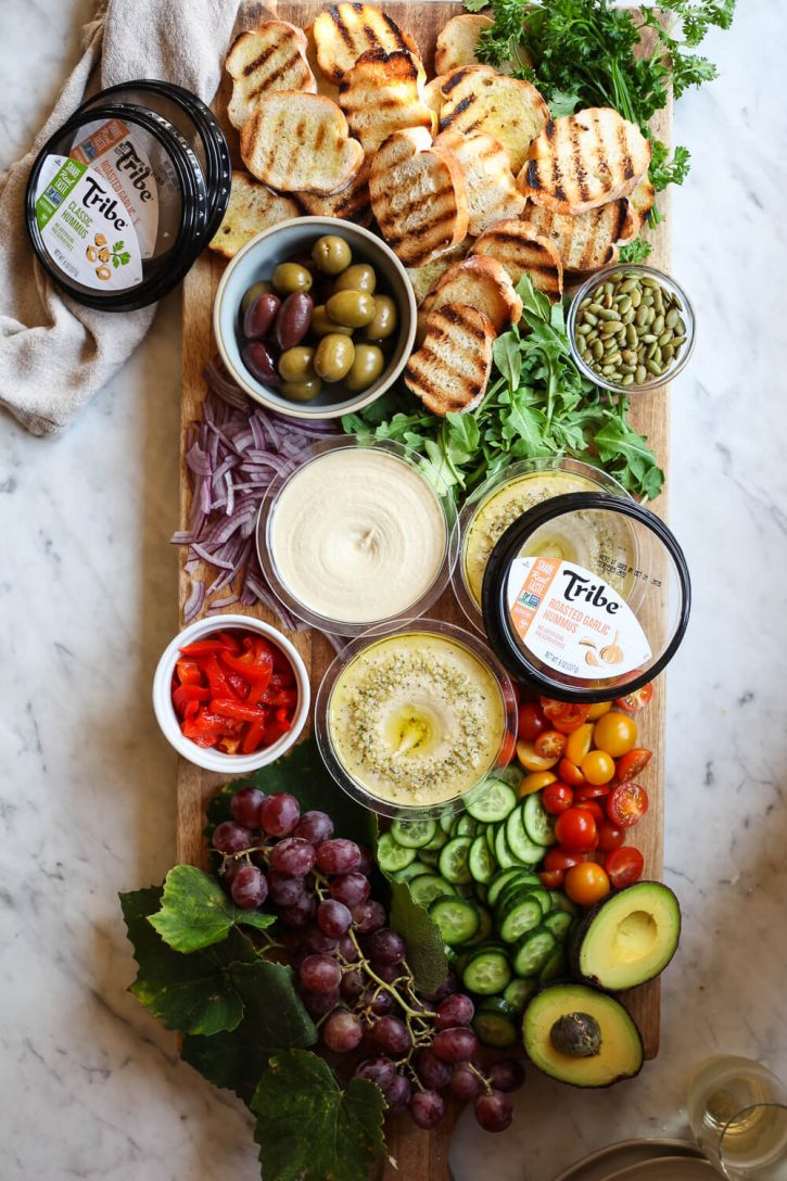 A beautiful charcuterie board topped with vegan ingredients like grilled crostini bread, hummus, peppers, cucumber, tomatoes, avocado, and arugula.