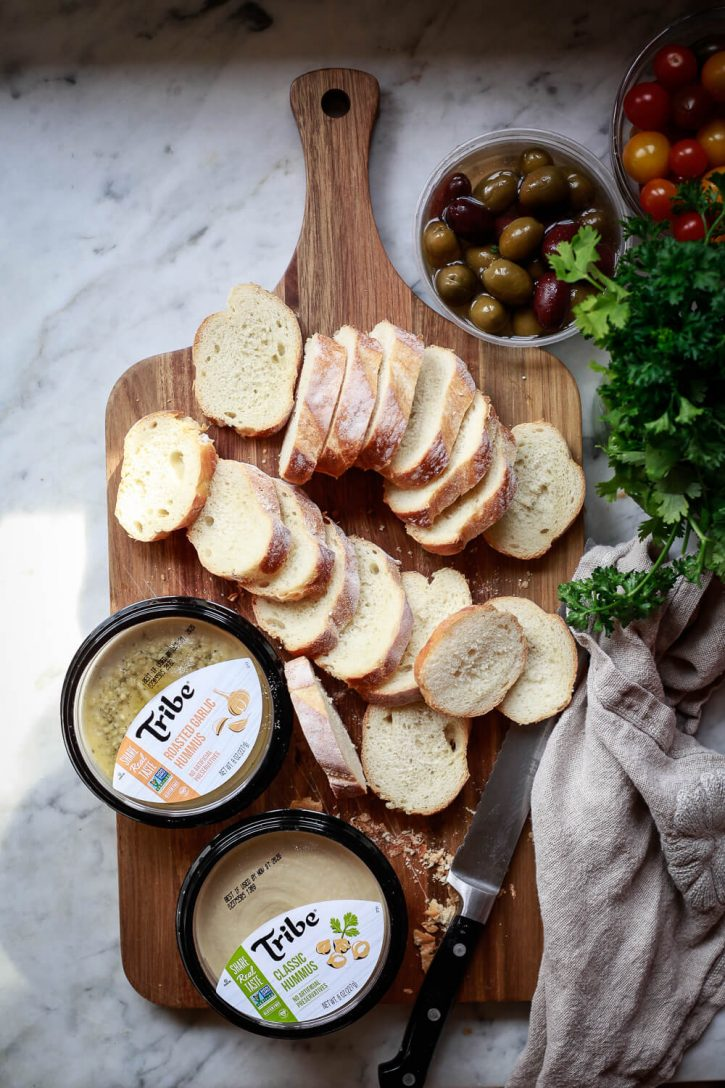 A baguette is sliced into rounds and sits on a cutting board with two tubs of Tribe hummus and a bowl of olives and tomatoes.