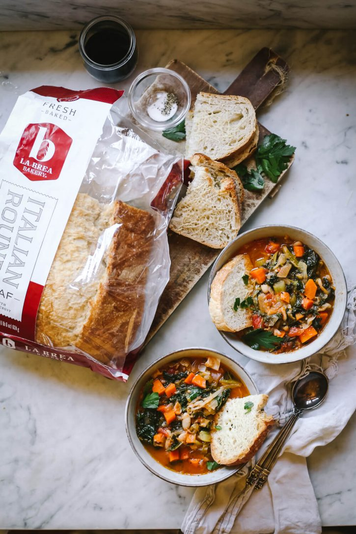 Two bowls of Tuscan ribollita soup on a marble countertop next to La Brea Italian round bread. This tuscan bread, vegetable, kale, and white bean soup is a healthy and delicious vegetarian/vegan comfort food meal.