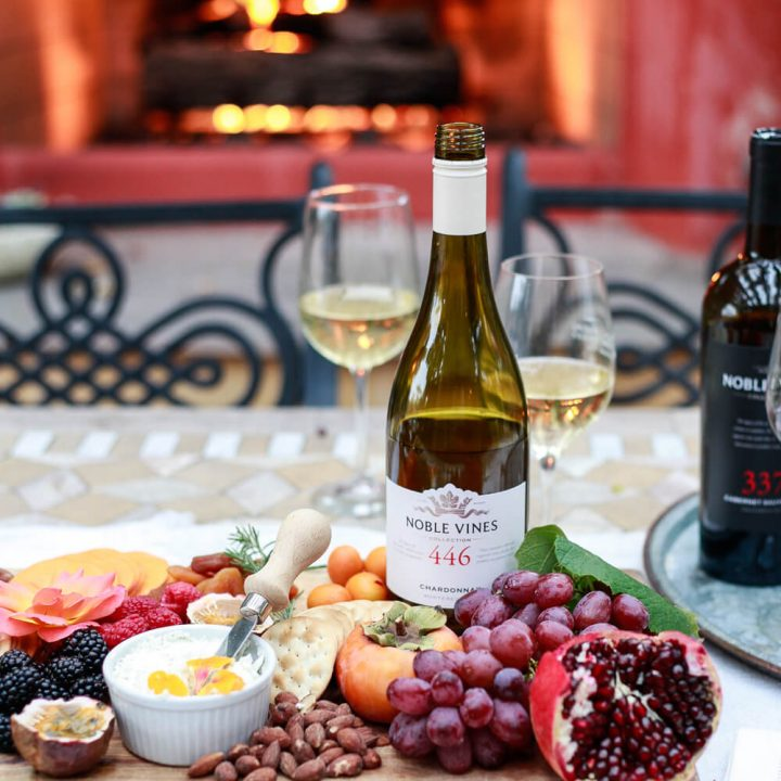 Wine and a charcuterie board on an outdoor table in front of a fire.