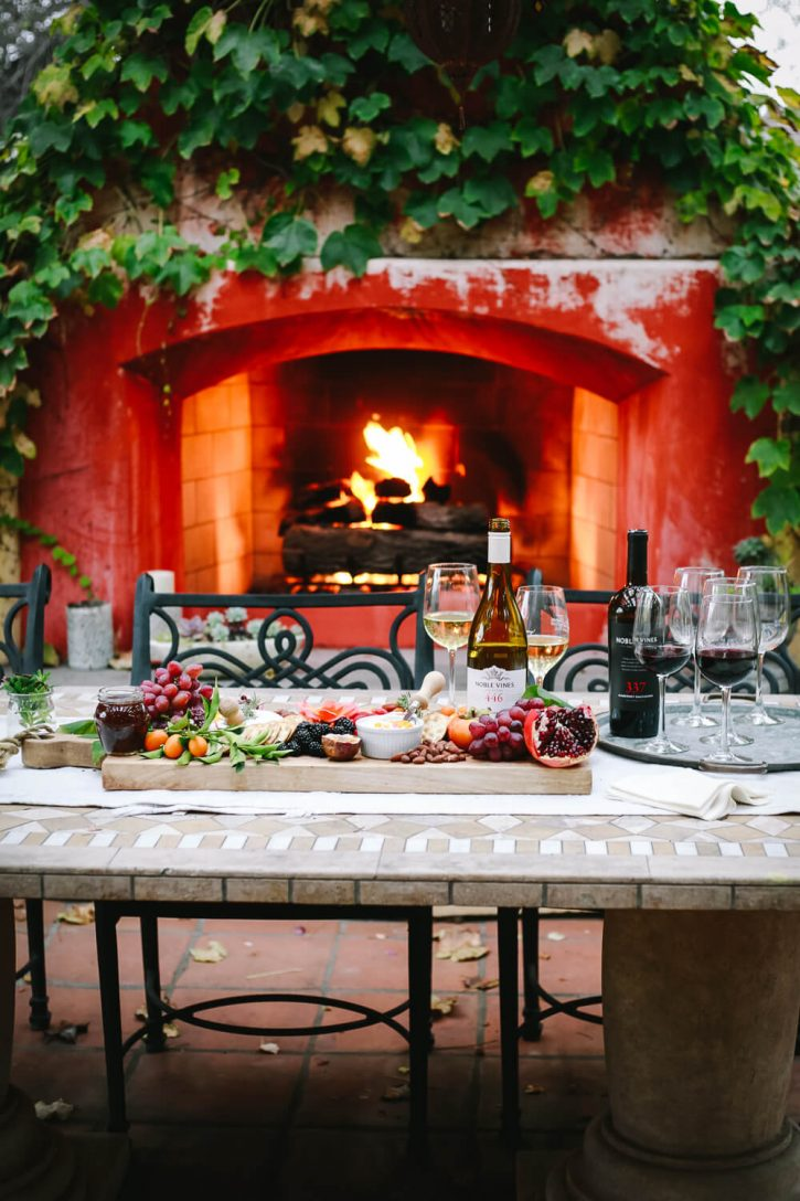 A beautiful outdoor table topped with a charcuterie board, wines, and wine glasses in front of a fireplace to show how to host a wine tasting party at home.
