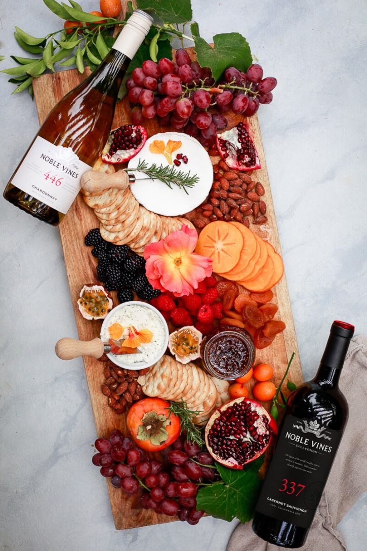 A beautiful charcuterie board with fruit, nuts, cheeses, and spreads.