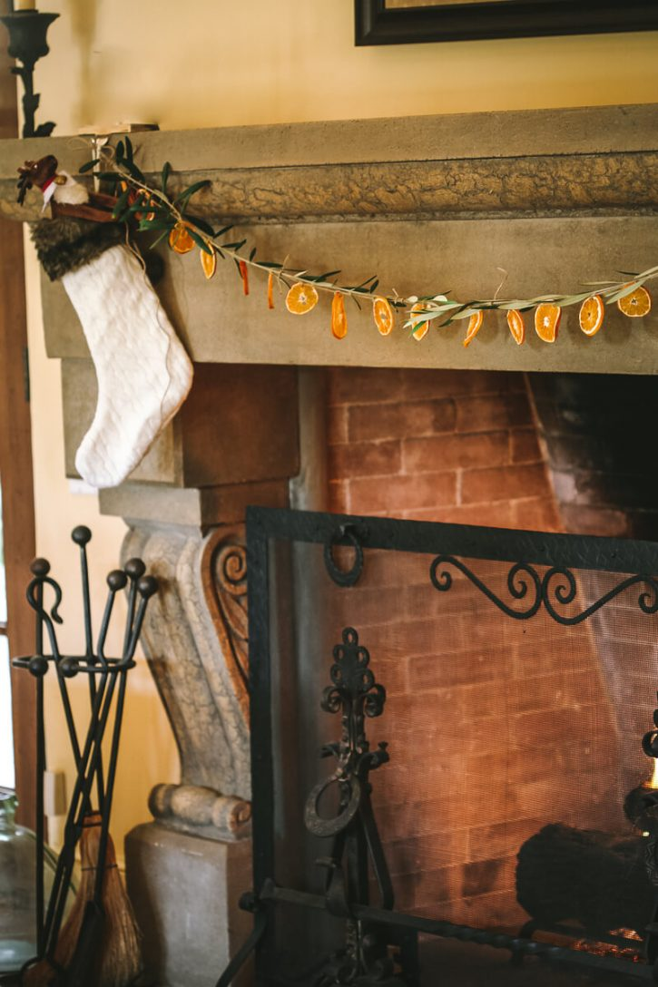 A beautiful homemade garland of dried orange slices and olive branches is hung over a large stone fireplace.