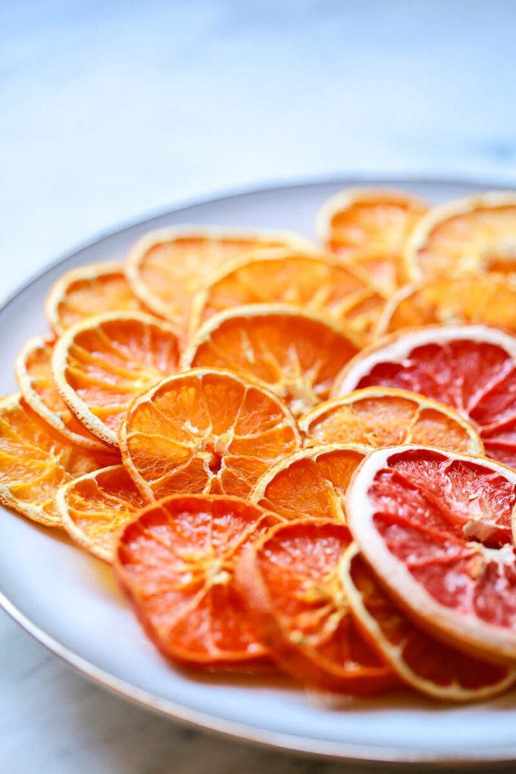 Beautiful dried orange slices on a white plate. Learn how to dry orange slices for garnishes, snacks, and Christmas ornaments and garlands.